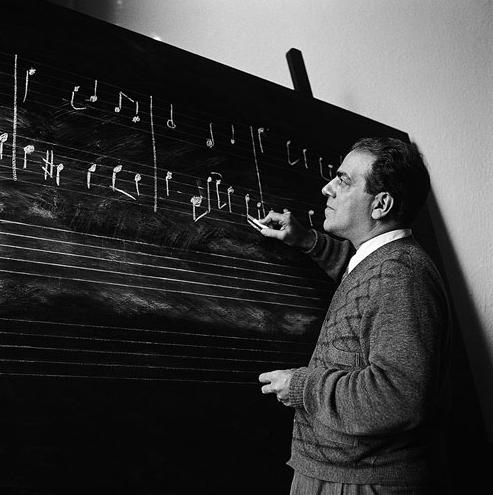 O Maestro Heitor Villa-Lobos desenhando notas musicais em lousa.