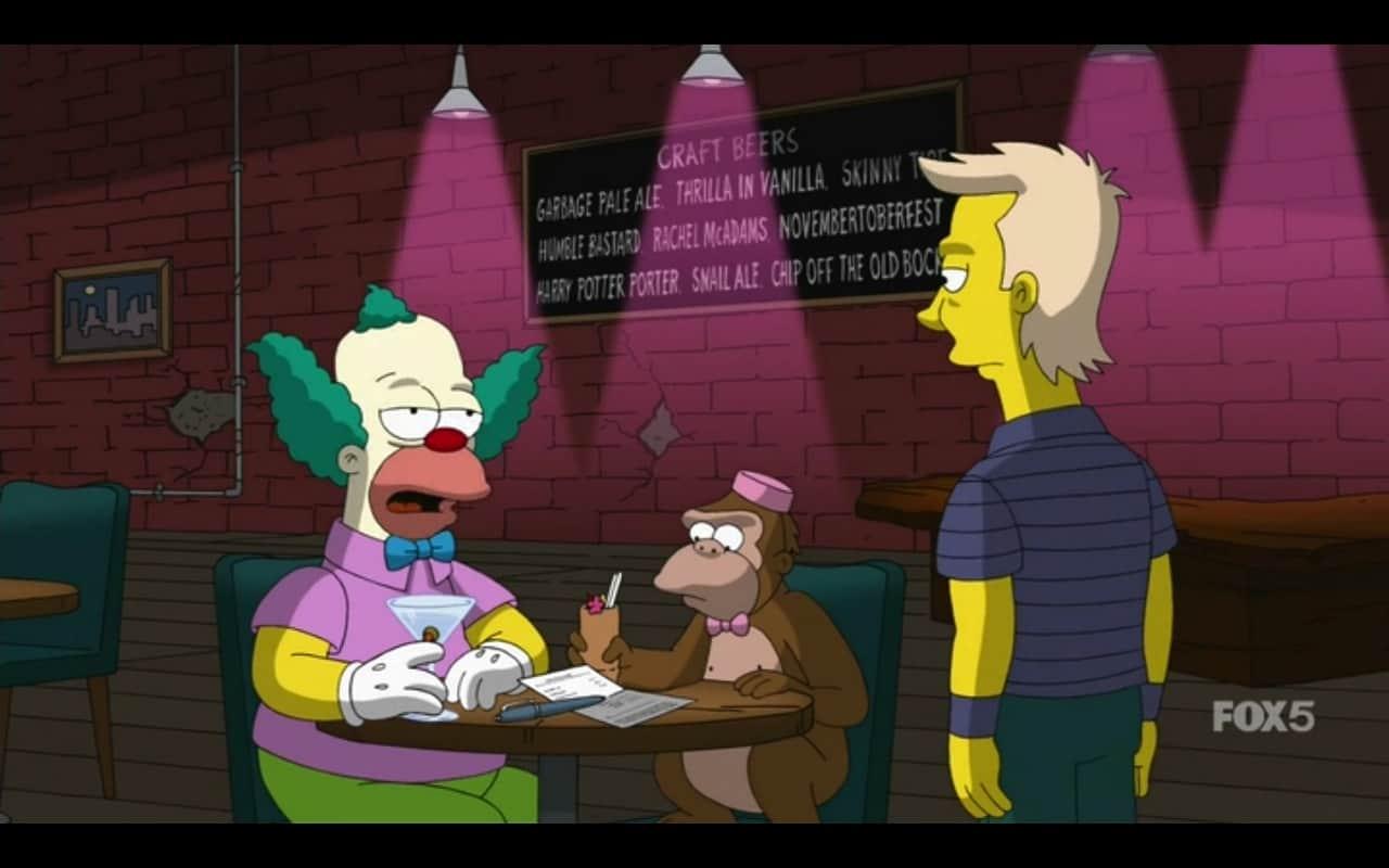 Palhaço e seu mascote em mesa conversam com garçom. Ao fundo, quadro com nomes de cervejas escritos