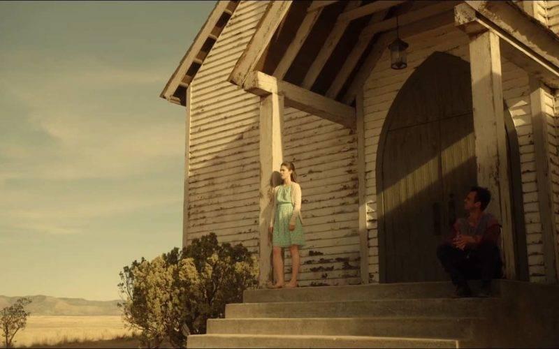 Jovem mulher em uma varanda, olhando para longe, enquanto um rapaz, sentado do outro lado olha e conversa com ela.