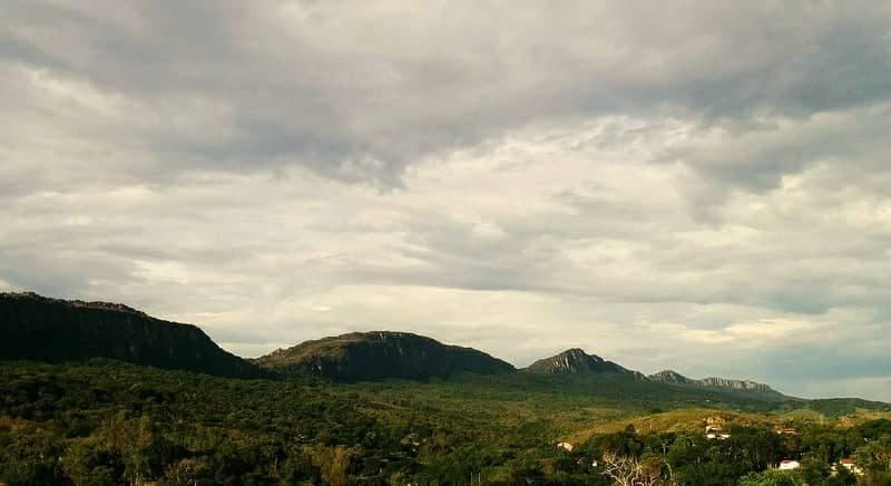 Conjunto de montanhase nuvens ao fundo, e cidade no primeiro plano