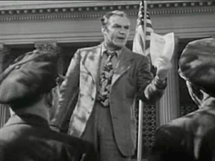 homem falando com fervor , em frente a uma bandeira americana e agitando um papel, enquanto observado por um público em uma praça