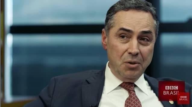 Homem de terno e gravata comentando com ênfase